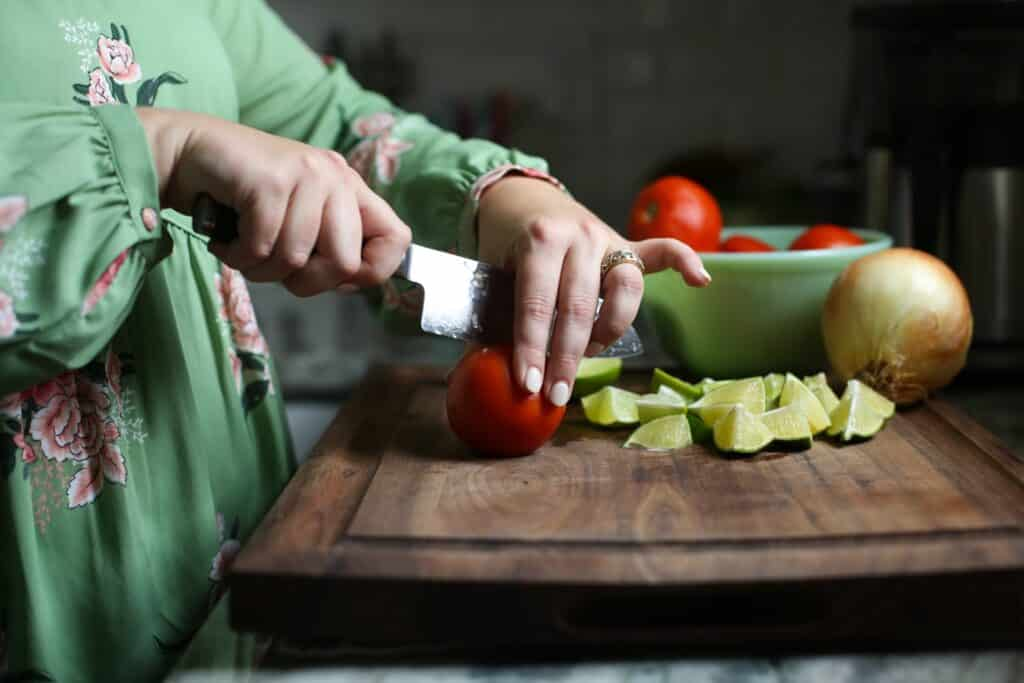 Hailey cutting vegetables on a wooden cutting board in her kitchen