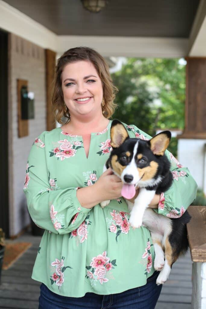 Hailey wearing a green shirt with pink flowers and holding a tri-colored corgi