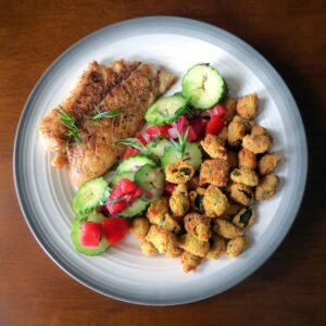 a fillet of cooked fish beside a serving of cucumber tomato salad and a pile of fried okra on a round dinner plate