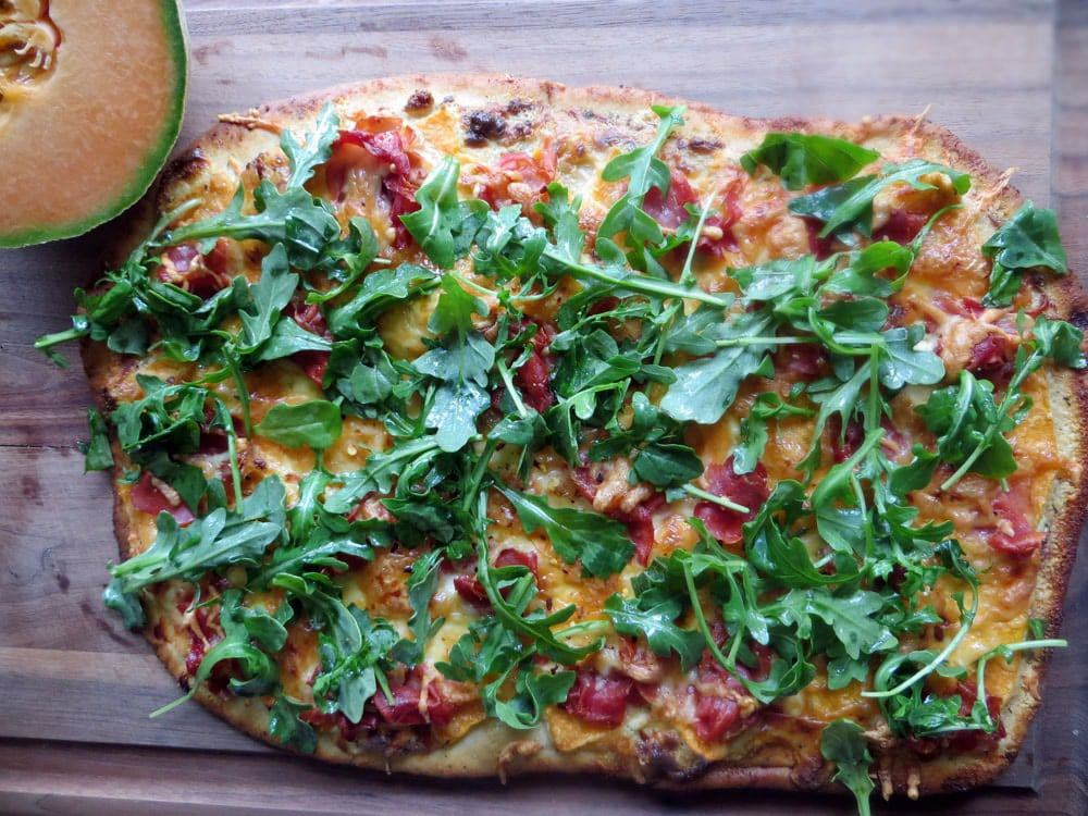 a rectangular shaped pizza with cooked meat and an abundance of fresh greens