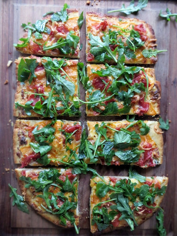 eight rectangular slices of pizza garnished with fresh greens and pieces of thinly sliced prosciutto