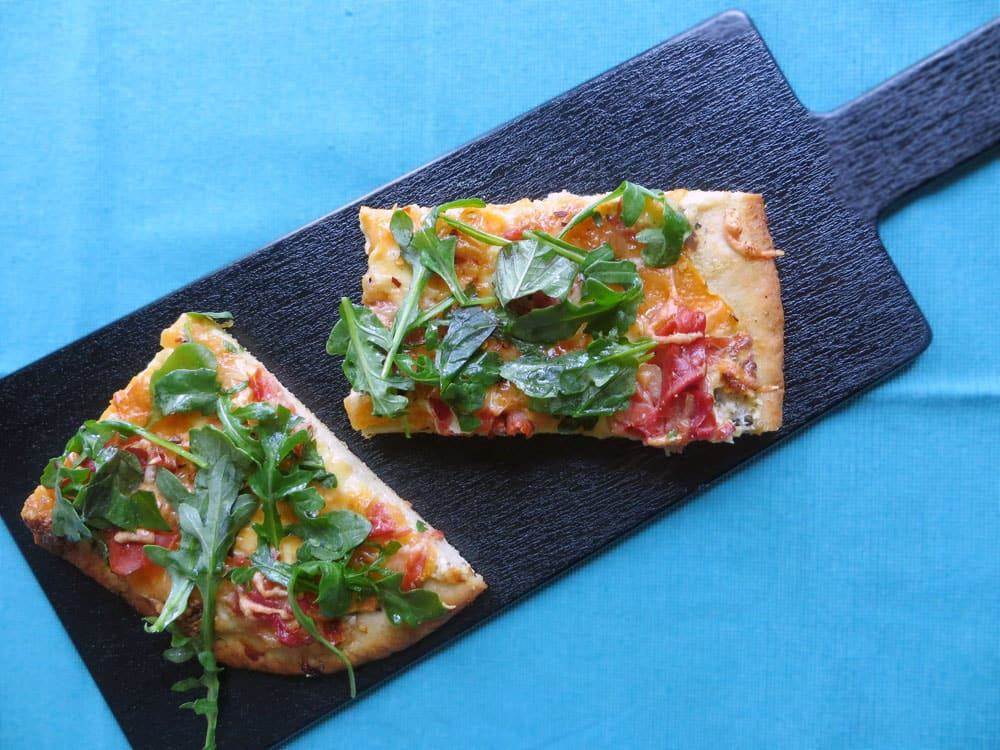 a black board holding two rectangular slices of pizza topped with fresh green arugula