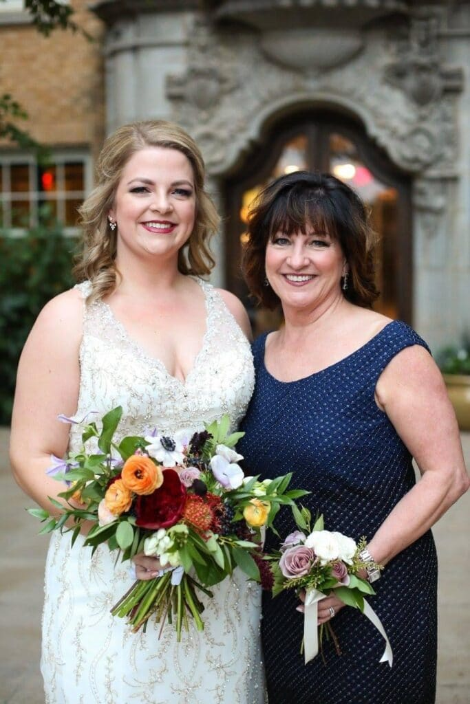 Two adult women, one in a wedding dress holding a bouquet and the other in a navy dress