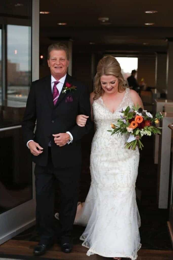 Adult man in a black suit walking with young adult female in a wedding dress