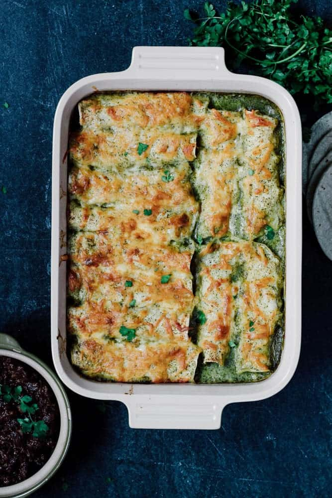 overhead view of Green Chicken Enchiladas in a rectangular casserole dish on a dark background