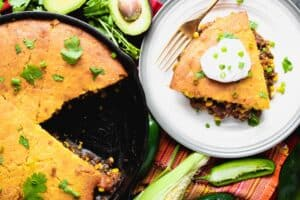 A sour cream topped wedge of cornbread over a mixture of meat and vegetables