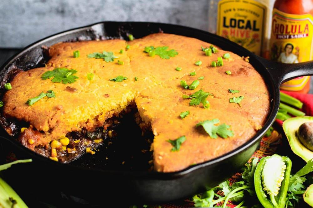 cornbread over meat and corn in a cast iron skillet