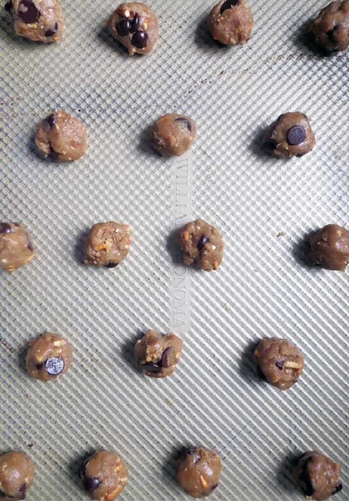 rows of balls of chocolate chip cookie dough on a textured metal surface