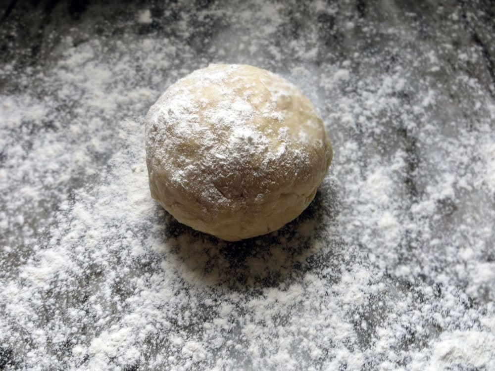 a ball of dough on a heavily floured marble countertop