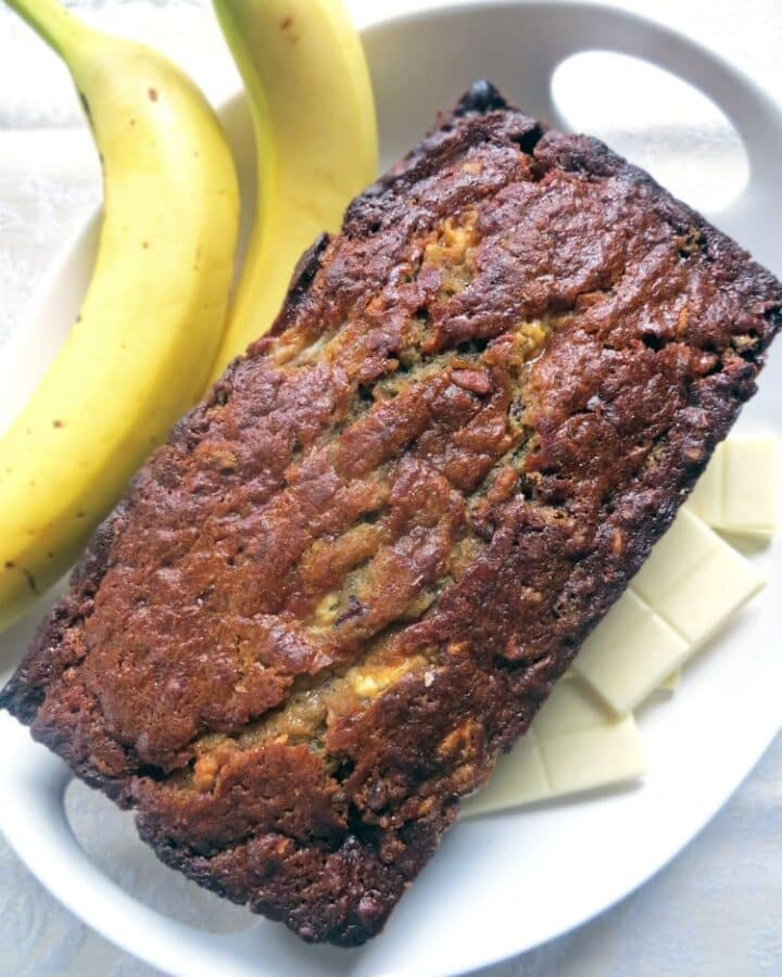 a loaf of baked banana bread on a white platter with squares of white chocolate and two unpeeled bananas on the side