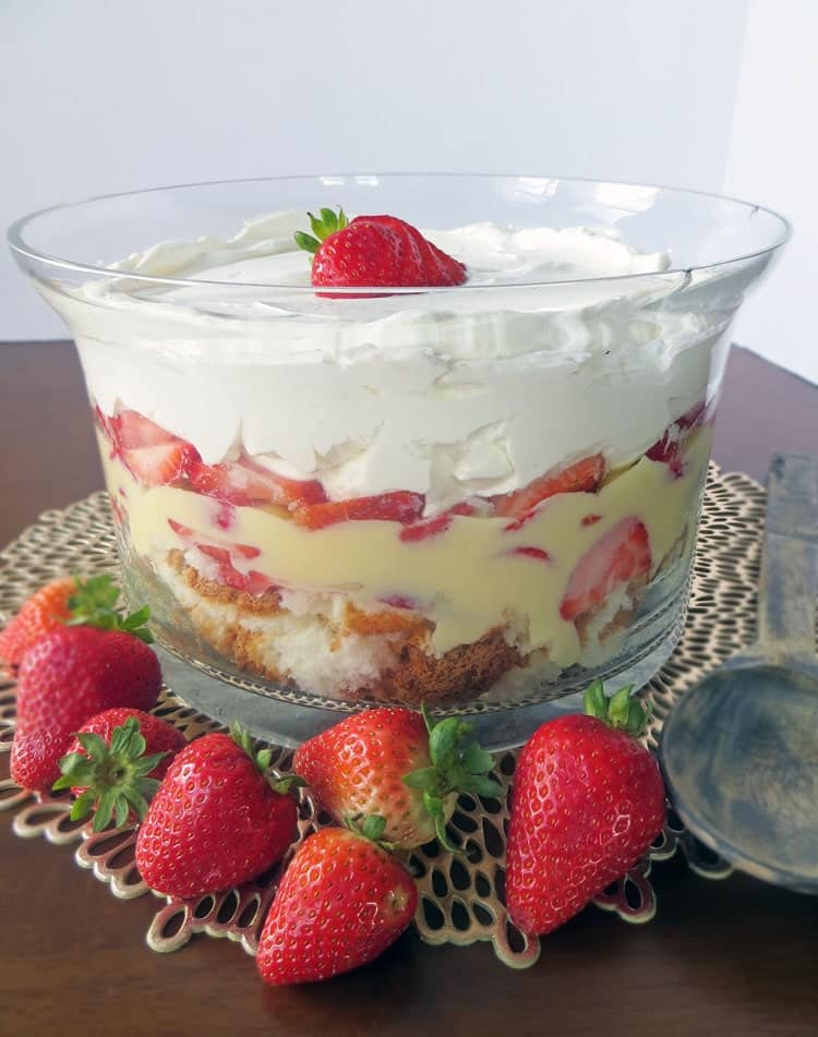 layers of pound cake, vanilla pudding, sliced strawberries, and whipped cream in a trifle bowl