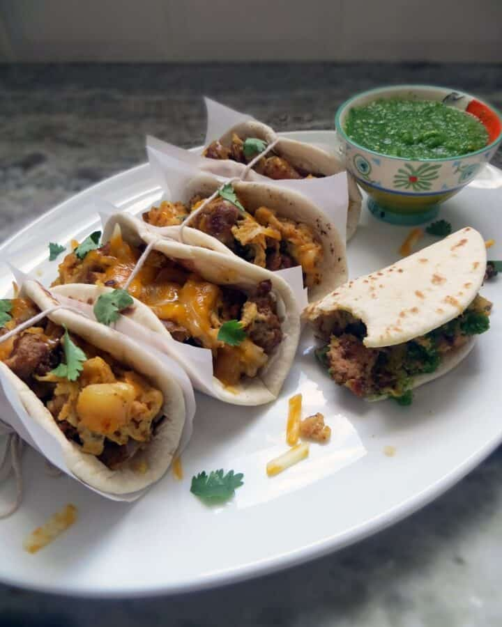 five tacos filled with meat and cheese beside a bowl of green sauce on an oval white platter