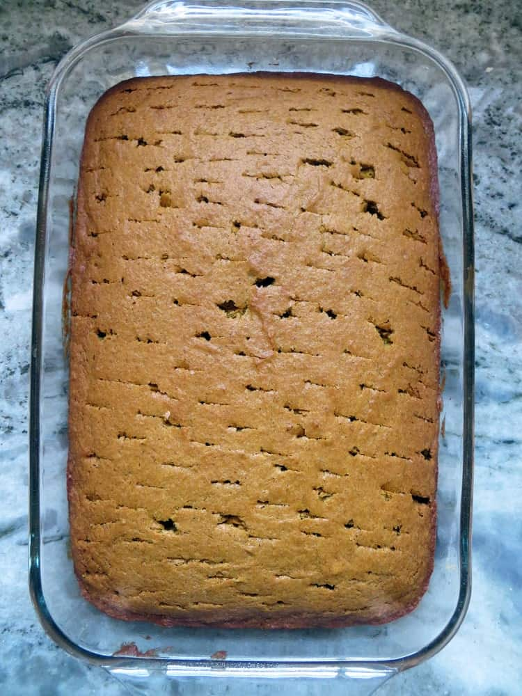 a light brown colored rectangular cake with holes pokes all over the surface