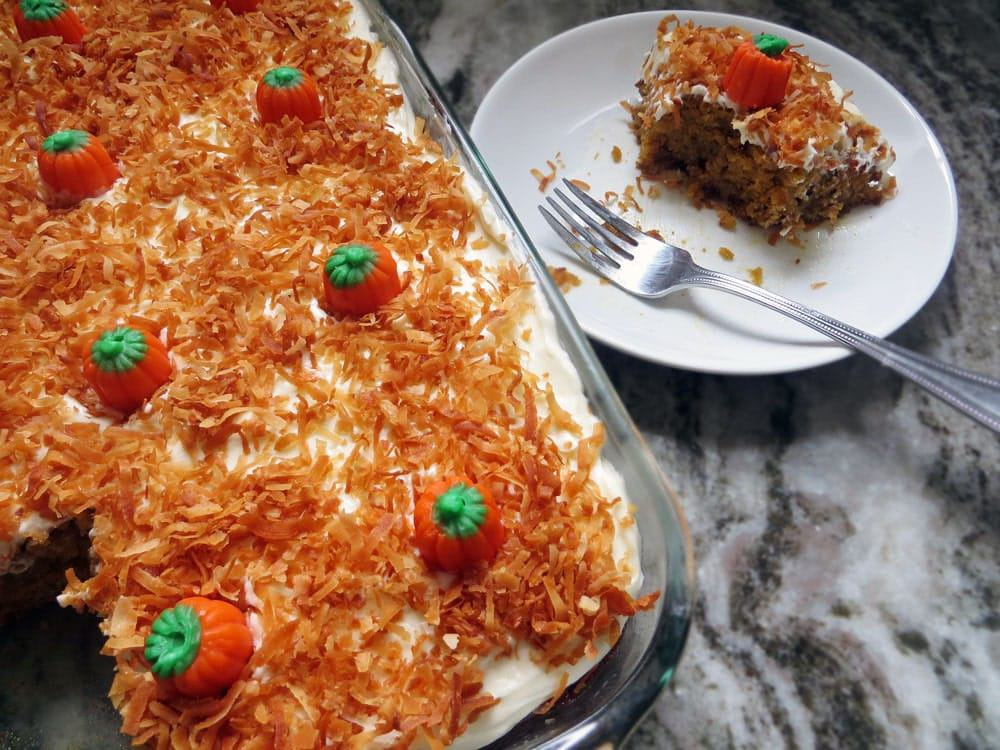 a cake topped with white frosting, orange colored coconut flakes, and mini pumpkin candies in a glass baking dish