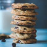 a stack of seven chocolate chip cookies with a glass of milk in the background