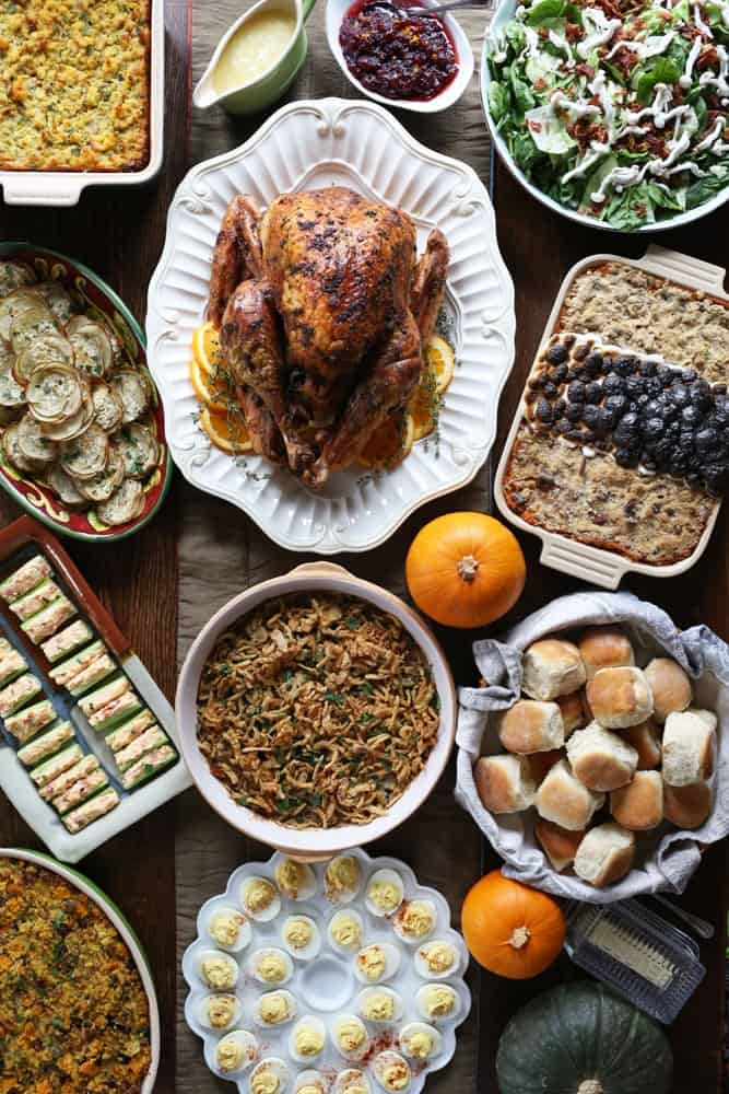 a spread of various Thanksgiving foods in serving dishes on a wooden table