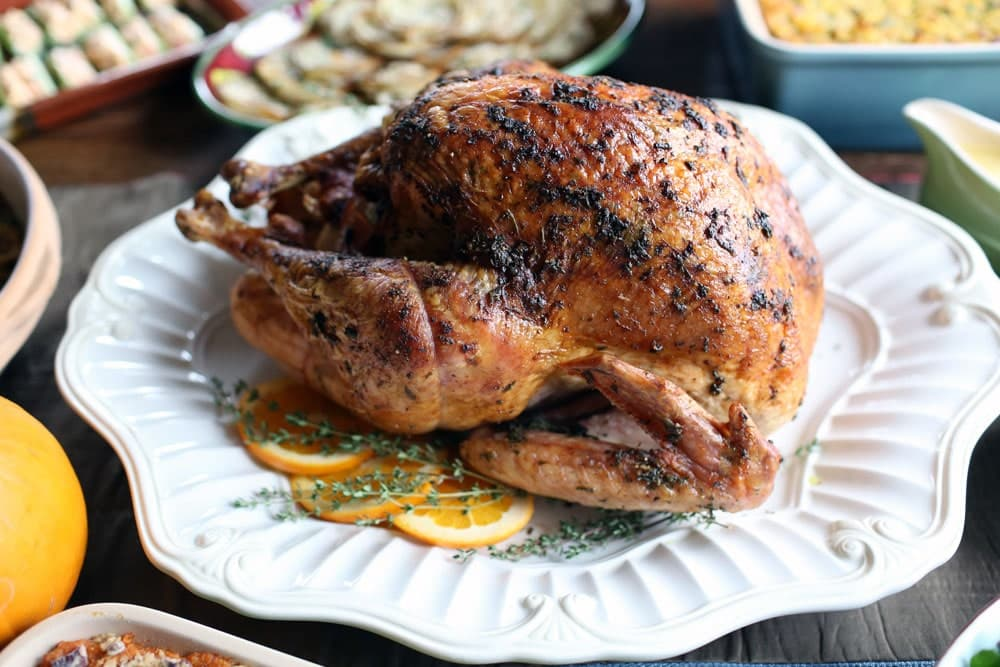 a cooked turkey served with slices of orange and sprigs of herbs on a white platter