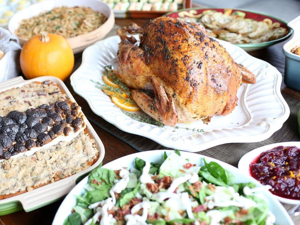 Thanksgiving herb butter turkey surrounded by side dishes on a Thnksgiving table