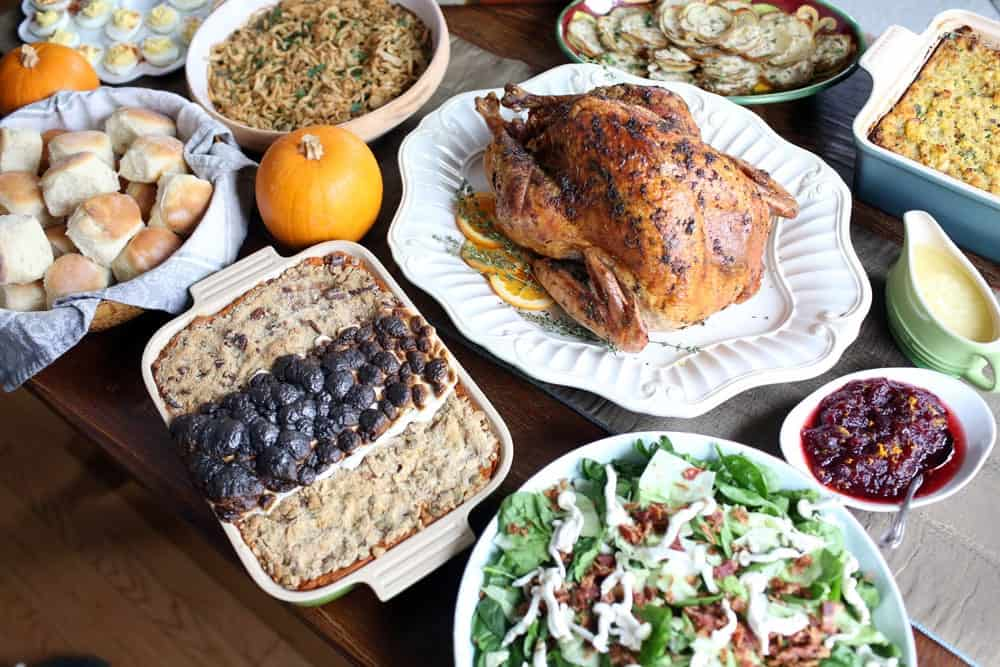 a cooked turkey on a platter surrounded by different side dishes on a wooden table
