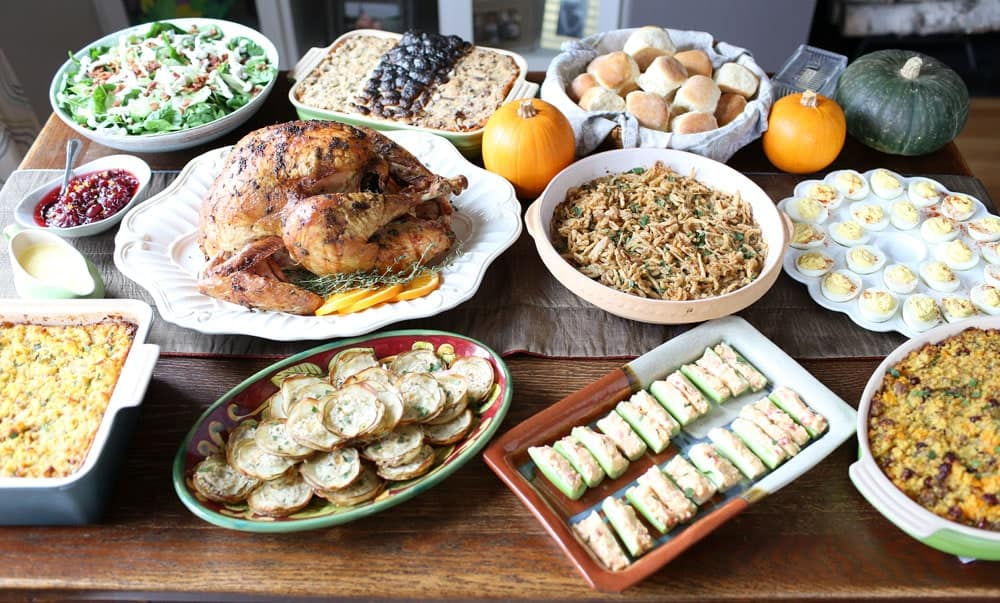 nine Thanksgiving dishes arranged on a wooden table decorated with small pumpkins