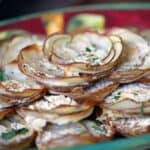 stacks of baked thin-sliced potato topped with creamy white cheese and sprinkled with green herbs