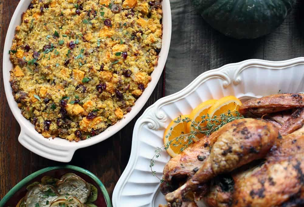 cornbread sausage dressing in an oval baking dish beside a cooked turkey on a white platter