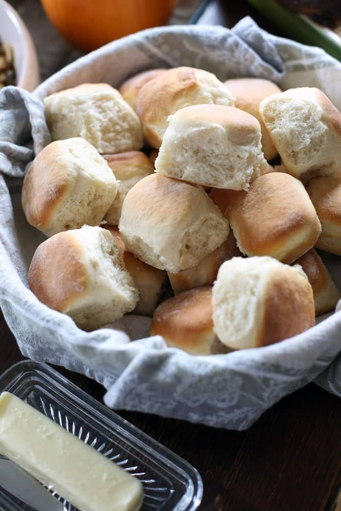 homemade dinner rolls in a bowl lined with a cloth towel