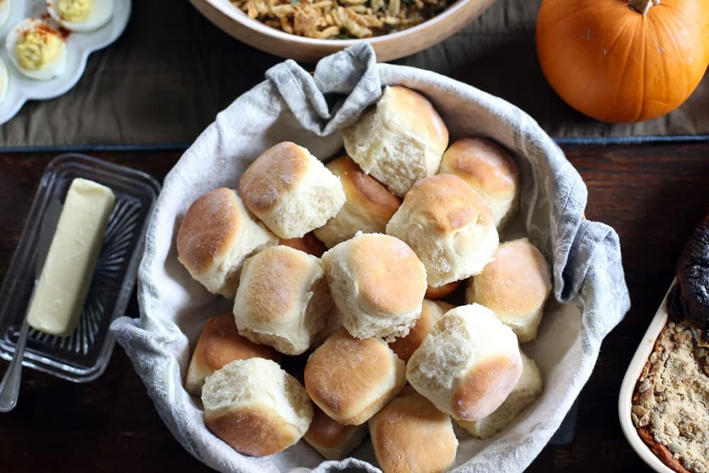 a large linen lined bowl filled with baked yeast rolls surrounded by a Thanksgiving dinner spread