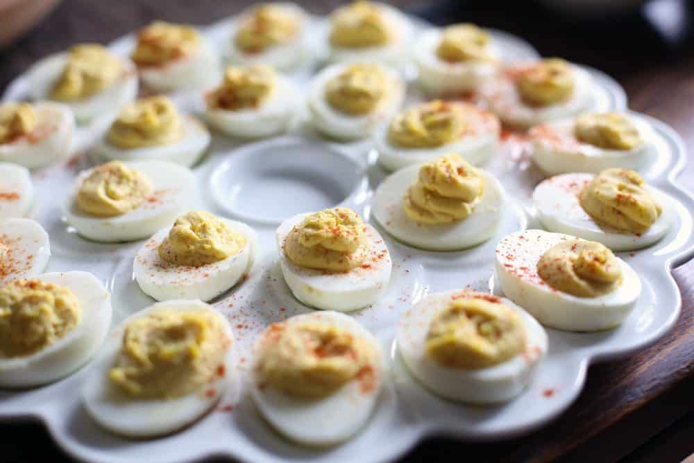 a tray of hard cooked egg halves filled with creamed egg yolk