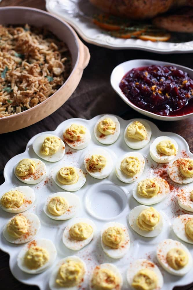 a tray of deviled eggs surrounded by other Thanksgiving side dishes