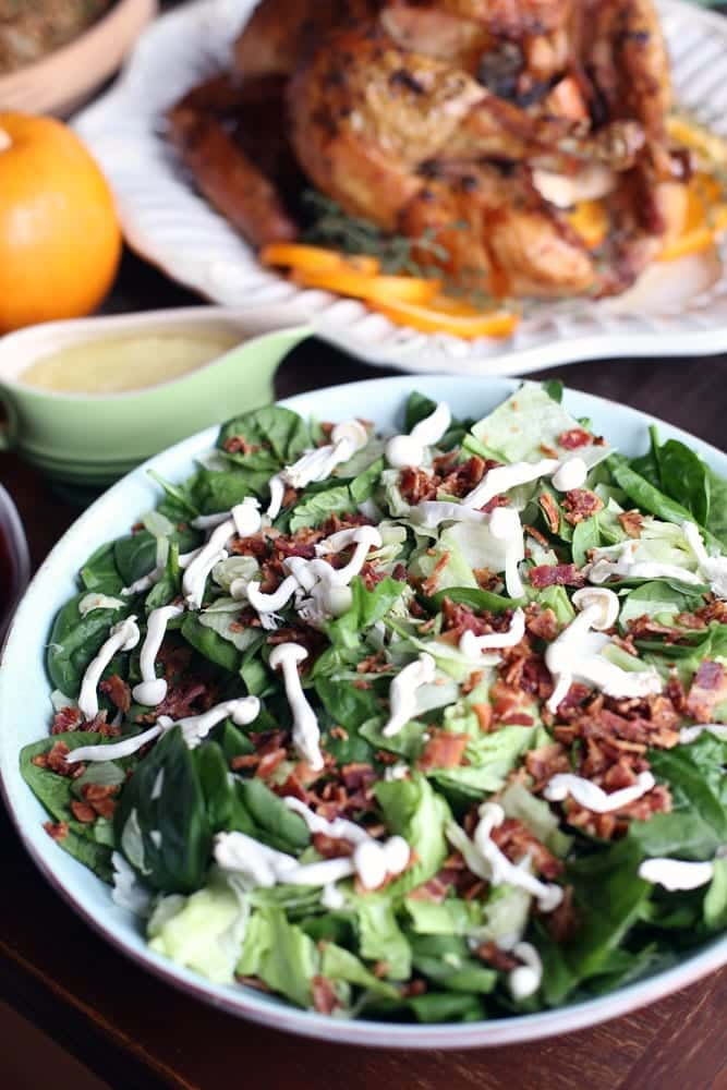 a bacon and mushroom spinach salad in a round white bowl