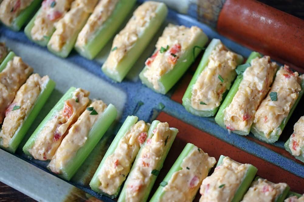 a platter lined with sticks of celery filled with creamy yellow cheese filling