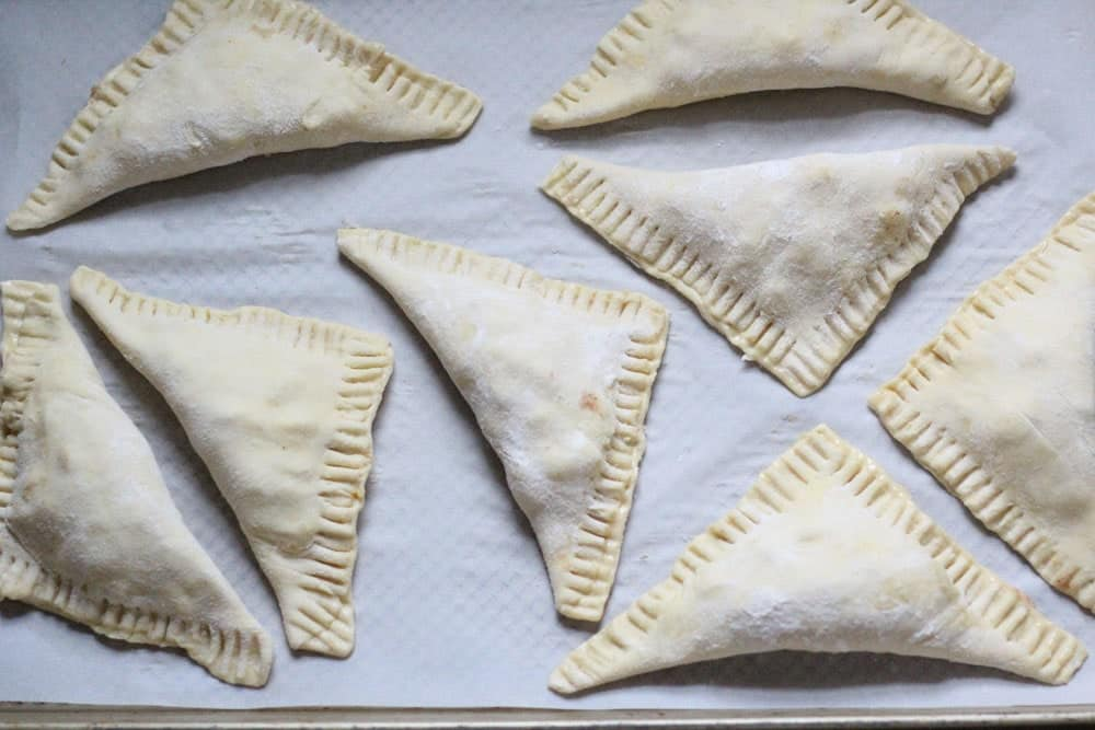 unbaked triangular pastries on a parchment lined baking sheet