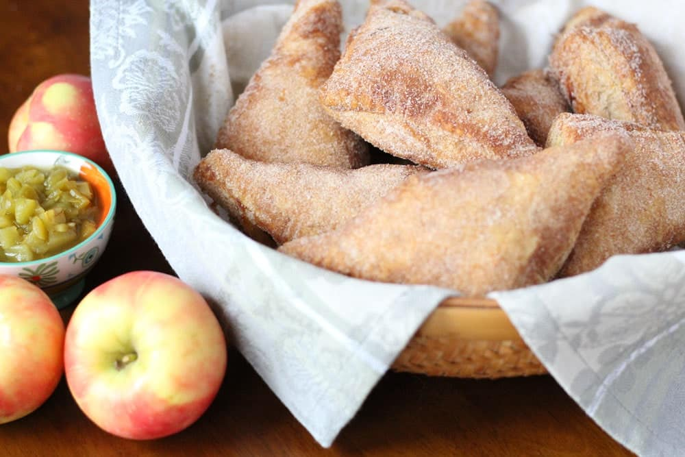 apple turnovers coated in sugar piled into a bowl lined with a linen napkin
