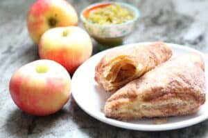 two sugared turnover pastries with apples and a bowl of diced green peppers