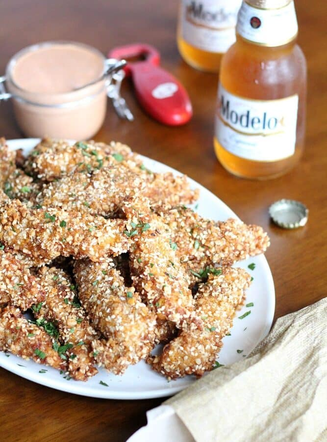 cornflake crusted chicken tenders stacked on an oval plate