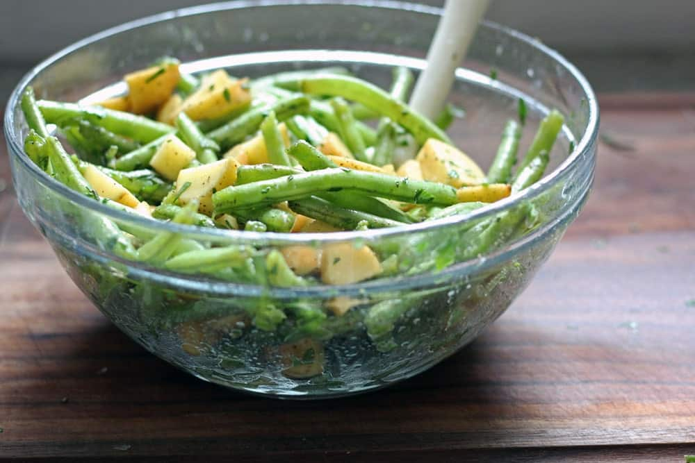 herbed green beans and cubed potatoes tossed together in a glass bowl