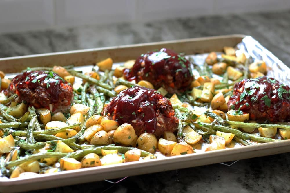 baked meatloaves topped with red sauce on a baking sheet with roasted potatoes and green beans