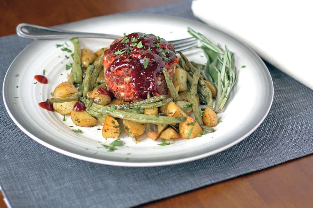 a small barbecued meatloaf on a bed of roasted potatoes and green beans served on a round plate
