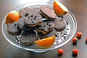 chocolate cookie sandwiches filled with orange frosting on a glass cake stand