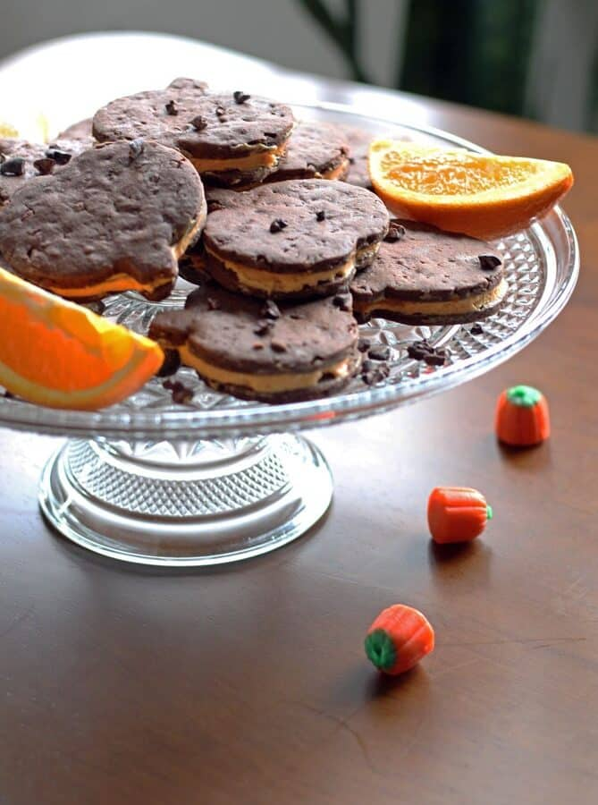 an ornate crystal cake stand piled with pumpkin shaped chocolate orange sandwich cookies