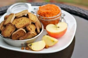 a bowl of baked dog biscuits on a plate with sliced apple and a jar of pumpkin puree