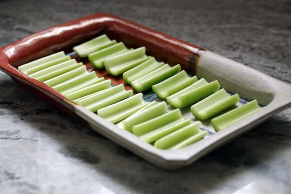 portions of celery lined side by side on a stone serving dish