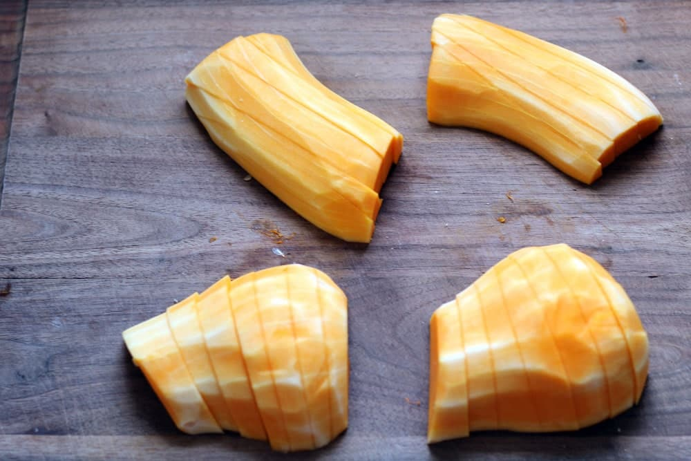 sliced peeled butternut squash on a wooden cutting board