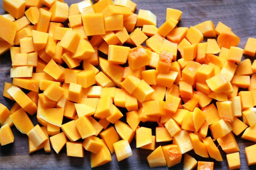 cubes of orange butternut squash piled on a wood cutting board