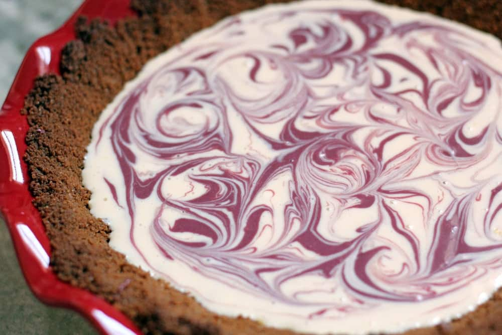 freshly poured cheesecake batter swirled with raspberry filling in a graham crust