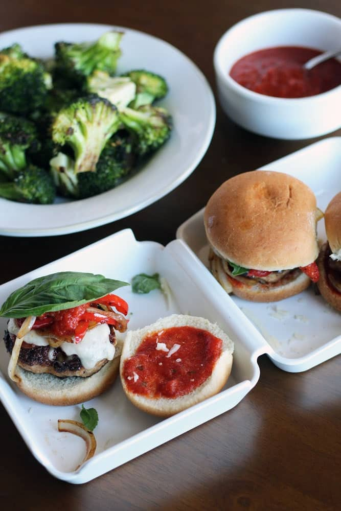 hamburger sliders on buns with marinara sauce, sauteed vegetables, and basil leaves on a white takeout box-style platter
