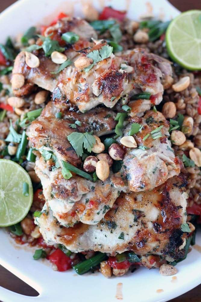 chicken breasts covered in vegetables, peanuts, and cilantro with lime halves on a white platter