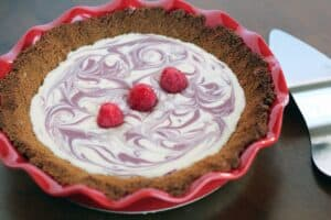 a pink and white swirled cheesecake with a graham cracker crust in a red pie dish