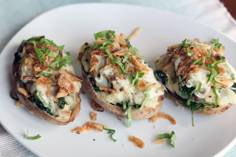 three baked potatoes stuffed and topped with French fried onions and thinly cut green herbs